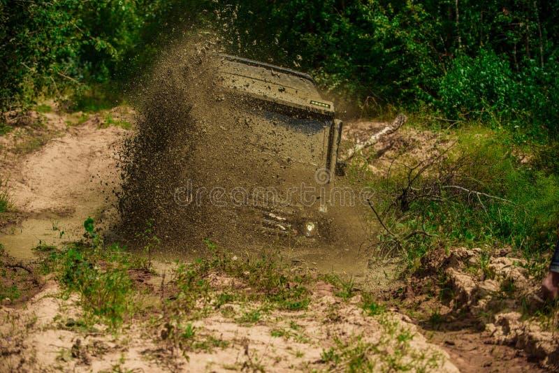 Modder en waterplons in het off-road rennen De jeep verpletterde in een vulklei en nam een nevel van vuil op Safari suv Reis stock fotografie