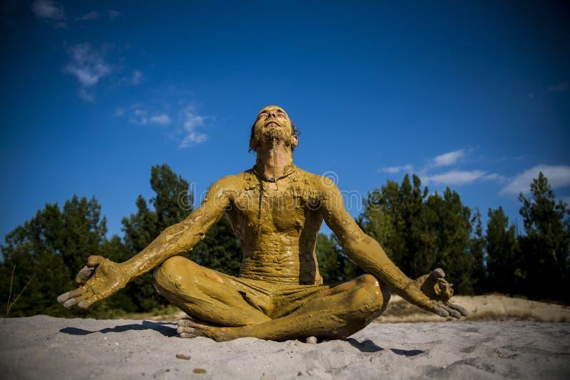 Modderdekking man do yoga in zand royalty-vrije stock afbeelding
