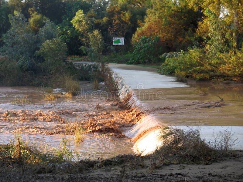 Modderig rivierwater die over concrete doorwaadbare plaats lopen stock fotografie