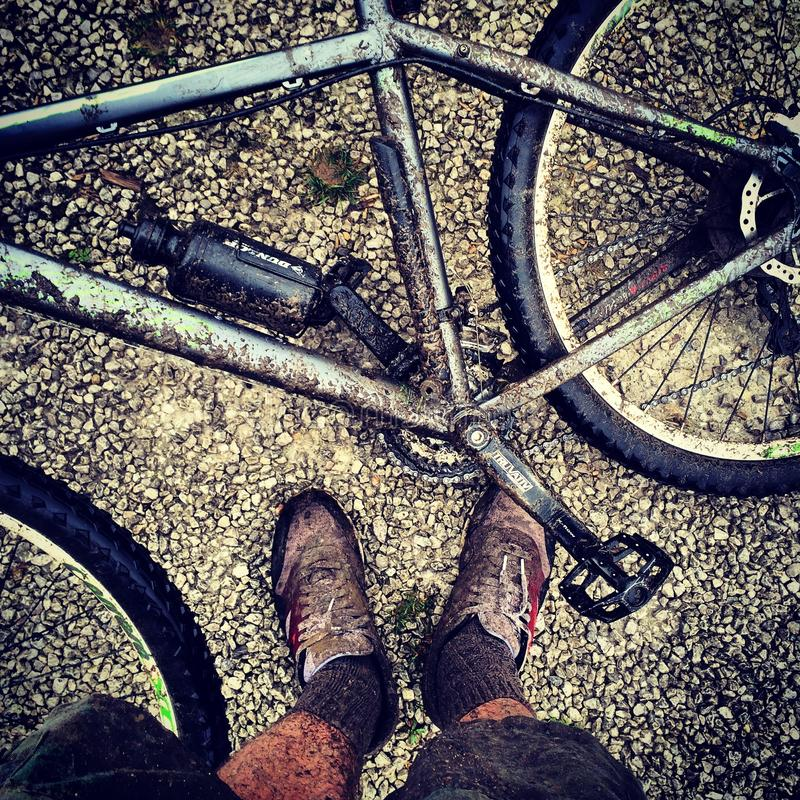 Modderige bergfiets met modderige voeten royalty-vrije stock afbeeldingen