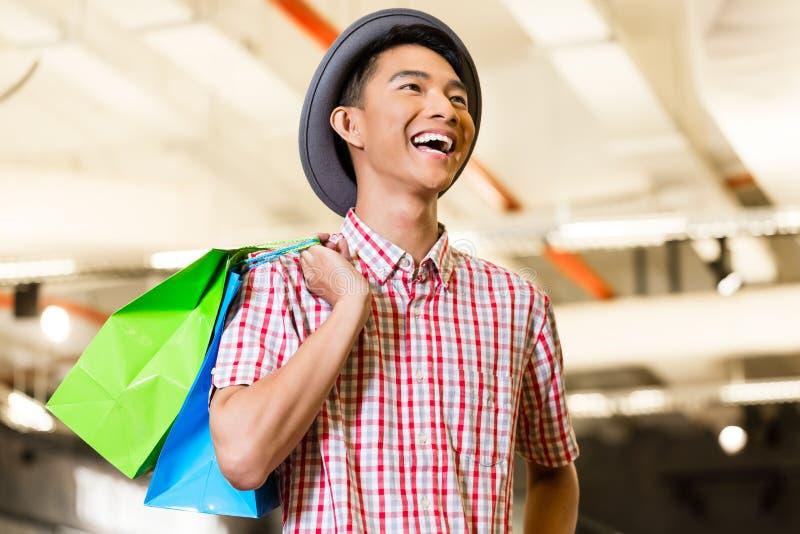 Mode asiatique d'achats de jeune homme dans le magasin images libres de droits