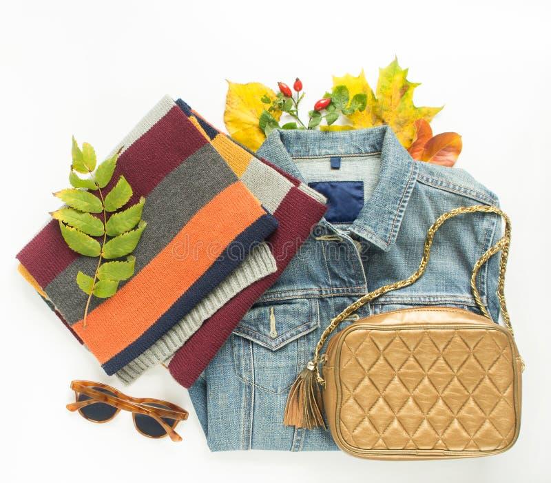 Mode d'automne, équipement d'automne de femme sur le fond blanc Veste bleue de denim, rétros lunettes de soleil, sac crossbody en photo stock