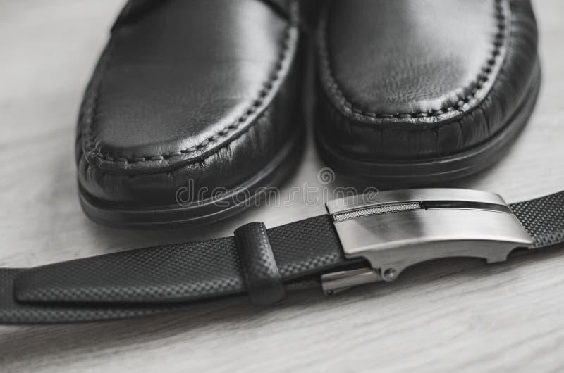 Mode d'hommes Accessoires d'hommes Chaussures noires et ceinture noire Durée toujours 1 Regard d'affaires sur un fond en bois photo libre de droits