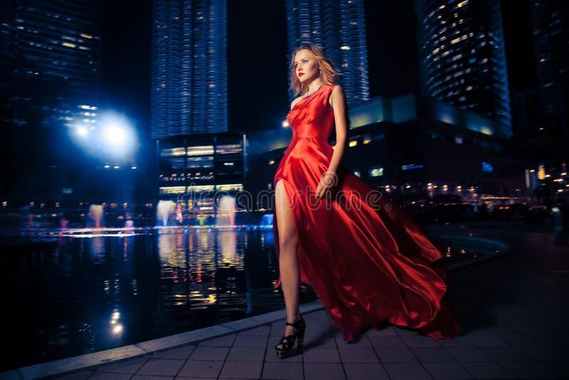 Mode-Dame In Red Dress und Stadt-Leuchten lizenzfreies stockfoto