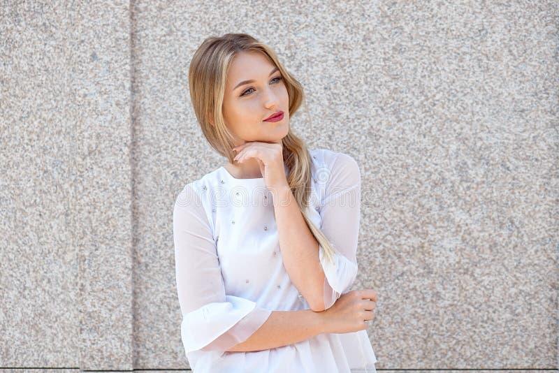 Mode de vie actif d'une jeune belle fille blonde d'étudiant dans la chemise blanche et le pantalon noir marchant pour travailler  photos libres de droits