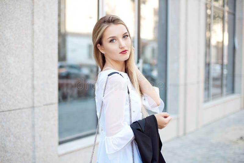 Mode de vie actif d'une jeune belle fille blonde d'étudiant dans la chemise blanche et le pantalon noir marchant pour travailler  photo libre de droits
