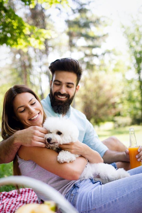 Mode de vie, couple heureux se reposant à un pique-nique en parc avec un chien photographie stock