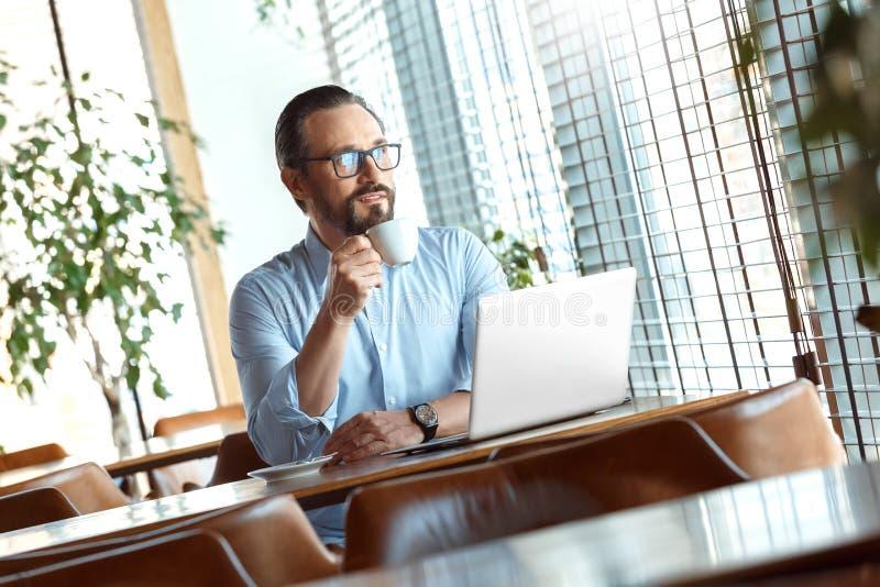 Mode de vie d'affaires Commerçant en verres se reposant au café avec l'ordinateur portable buvant du café chaud appréciant la vue photos stock