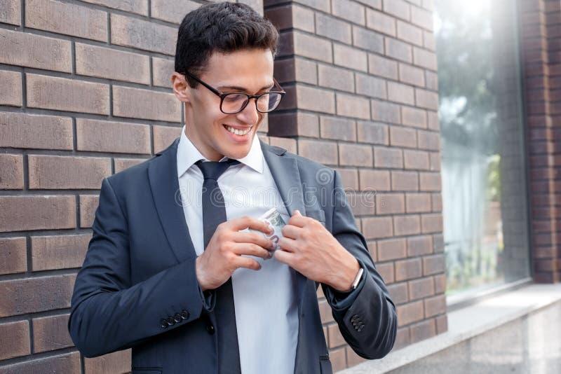 Mode de vie d'affaires Homme d'affaires dans des lunettes se tenant sur la rue de ville mettant le salaire dans la poche gaie photos libres de droits