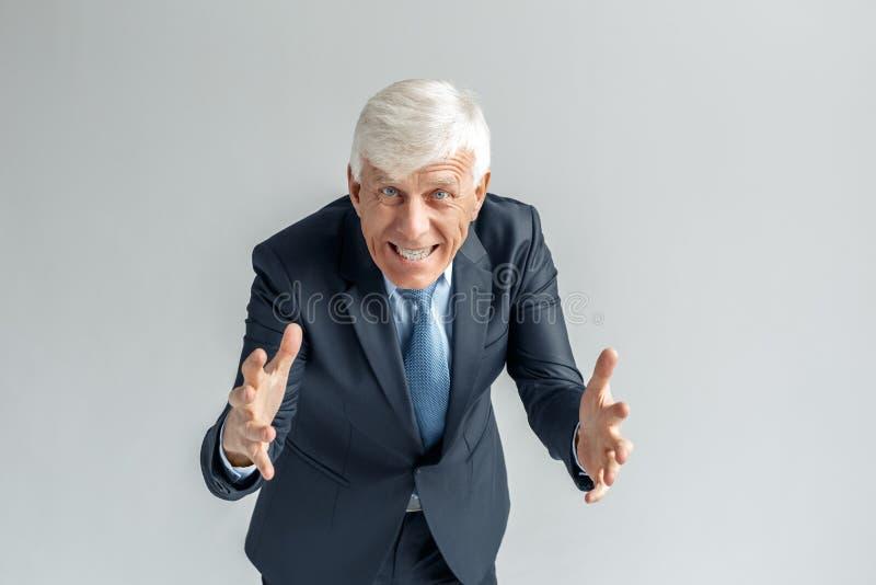 Mode de vie d'affaires Position d'homme d'affaires d'isolement sur faire des gestes gris au plan rapproché toothy de sourire de c photos libres de droits