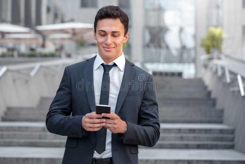 Mode de vie d'affaires Position d'homme d'affaires sur la rue de ville vérifiant des médias sur le smartphone joyeux photos stock