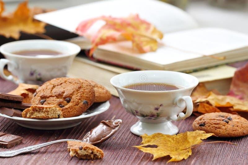 Mode de vie d'automne avec le thé, les bonbons et les feuilles chauds de jaune photographie stock libre de droits