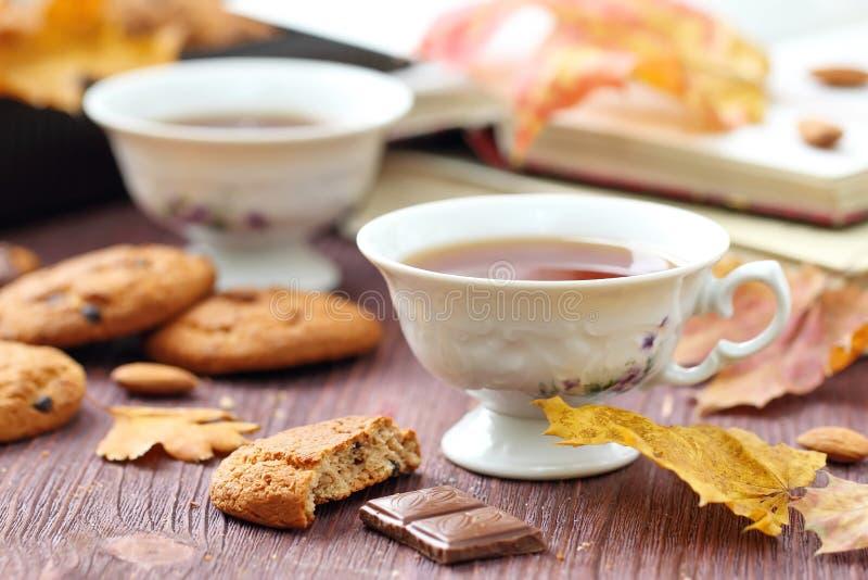 Mode de vie d'automne avec le thé, les bonbons et les feuilles chauds de jaune image libre de droits