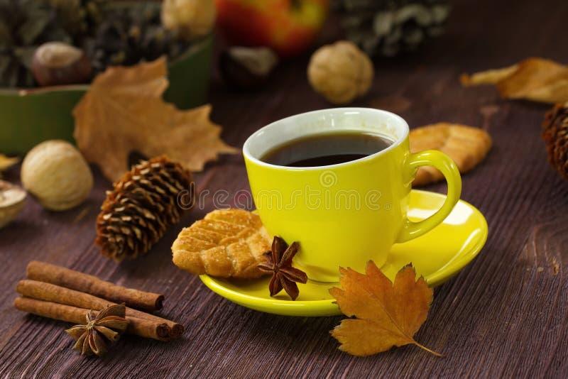 Mode de vie d'automne avec le thé, les bonbons, les écrous et les feuilles chauds de jaune photo stock