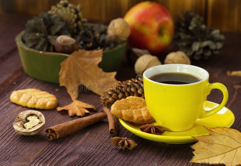 Mode de vie d'automne avec le thé, les bonbons, les écrous et les feuilles chauds de jaune image stock