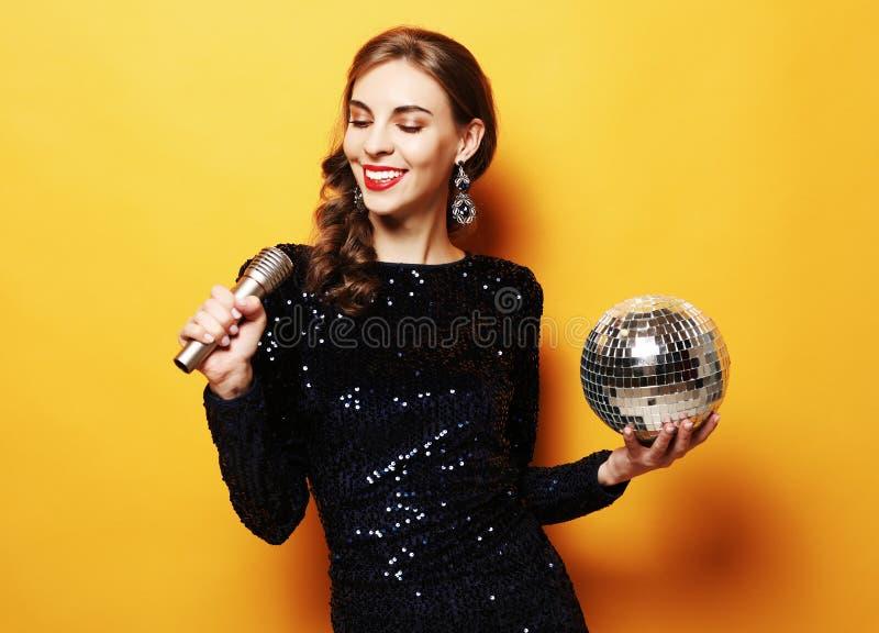 Mode de vie et concept de personnes - femme dans le microphone de participation de robe de soir?e et la boule de disco photos stock