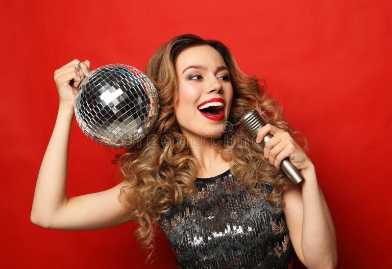 Mode de vie et concept de personnes - femme dans le microphone de participation de robe de soir?e et la boule de disco photographie stock libre de droits