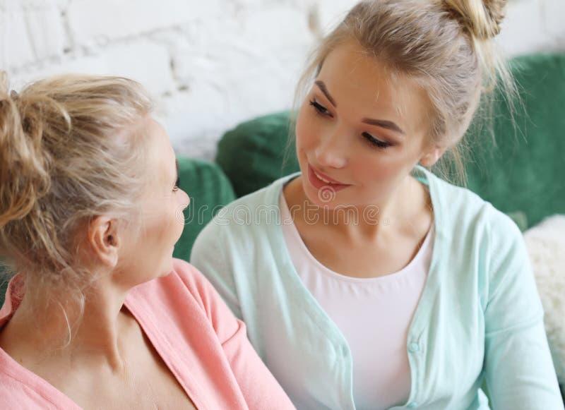 Mode de vie et concept de personnes : Femme supérieure avec la fille adulte détendant sur Sofa At Home image stock