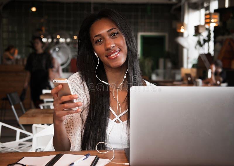 Mode de vie et concept de personnes : portrait de jeune femme africaine heureuse dans un café utilisant le téléphone portable et  photo stock