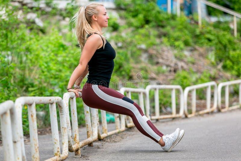 Mode de vie de forme physique Jeune femme faisant des pous?es du pilier Jeune fille blonde sportive un jour ensoleill? au stade S images libres de droits