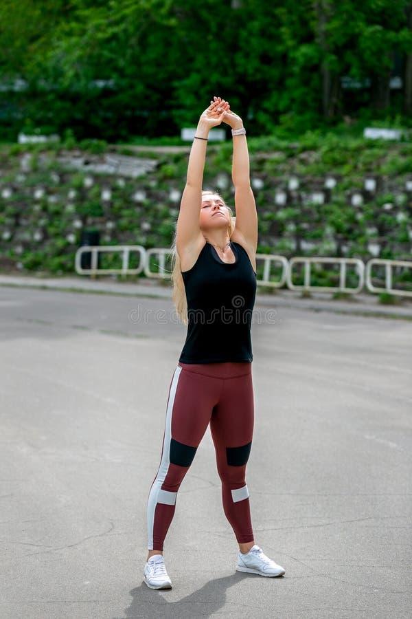 Mode de vie de forme physique La jeune femme r?chauffant avant faire s'exer?ant s'exerce pour ?tirer ses muscles et joints Jeune  photo libre de droits