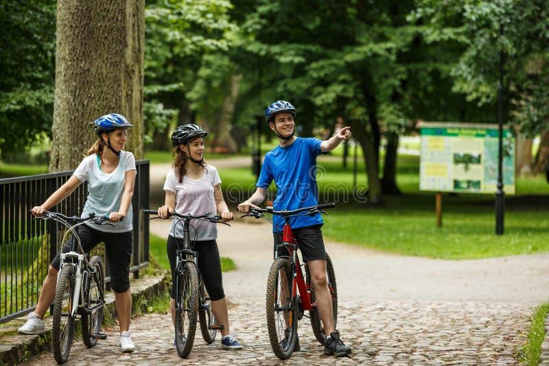 Mode de vie sain - bicyclettes de monte de personnes en parc de ville photo stock