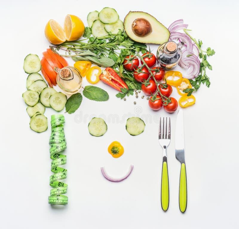 Mode de vie sain et concept suivant un régime Visage amical fait de divers légumes de salade, couverts et bande de mesure sur le  image stock