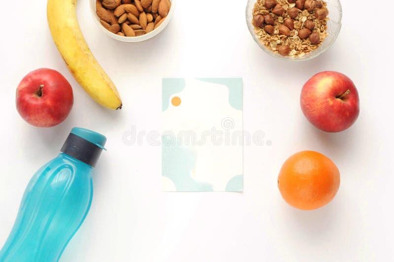Mode de vie sain : nourriture sur le fond blanc avec la note Vue plate avec l'espace de copie Bouteille, écrous, farine d'avoine  photo stock