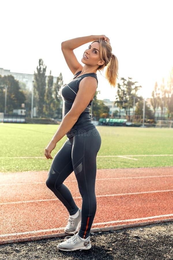 Mode de vie sportif Jeune femme sur la position de stade sur la voie posant tir joyeux de corps de caméra au plein photographie stock libre de droits