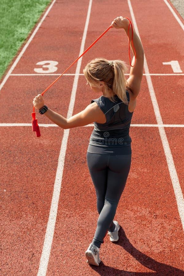 Mode de vie sportif Jeune femme sur la position de stade sur la voie stratching avec la vue arrière supérieure de corde de saut photos stock