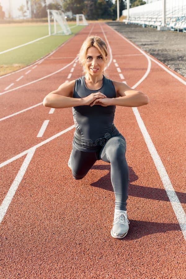 Mode de vie sportif Jeune femme sur le pas en avant de stade étirant la jambe sur le sourire de voie motivé photographie stock