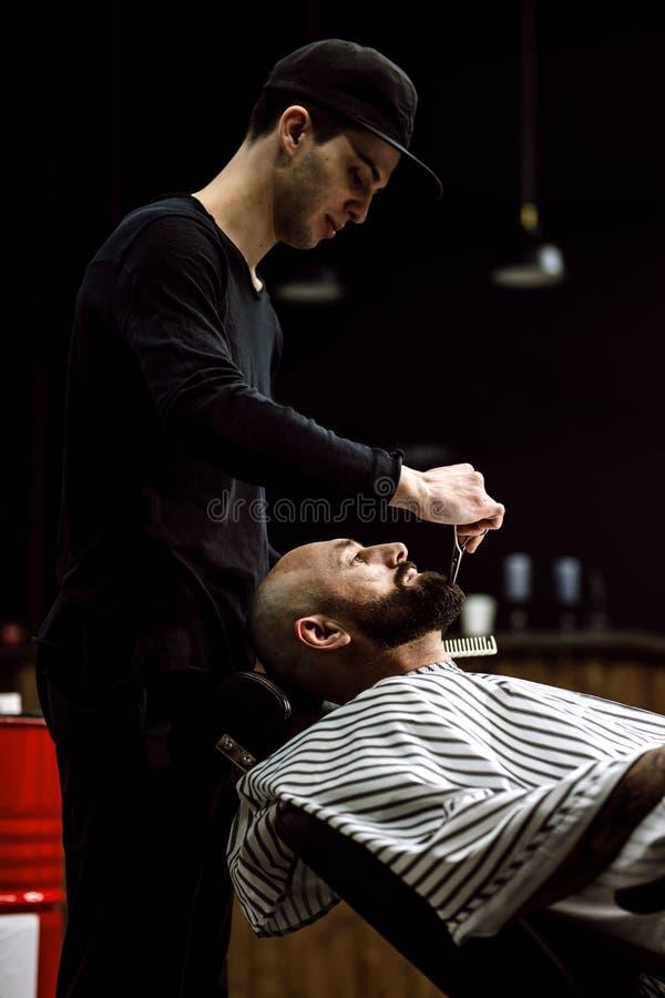 Mode du ` s d'hommes Le coiffeur s'est habillé dans une barbe noire de ciseaux de vêtements d'homme brutal dans le raseur-coiffeu photos stock