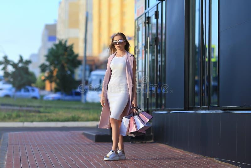 Mode-Einkaufsmädchen-Porträt Schönes Mädchen in den Sonnenbrillen Nach dem Tageseinkaufen Mädchen mit Einkaufenbeuteln - Sally kä stockbild