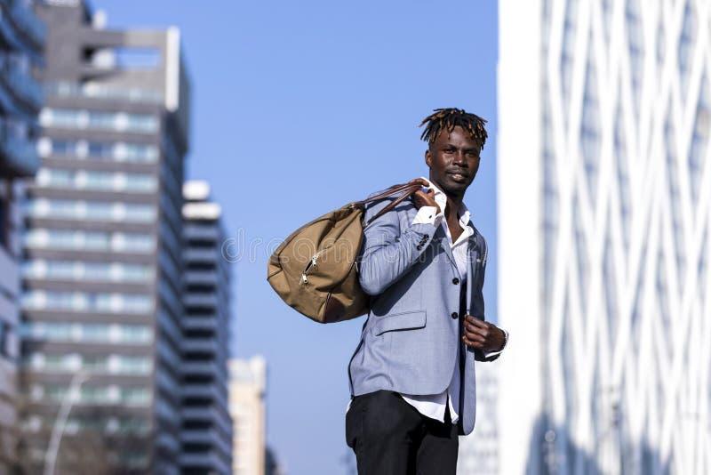 Mode för ung man för svart för främre sikt stads- tillfälligt i gatan Bärande svart elegant omslag, jeans och att rymma och bära  royaltyfri foto