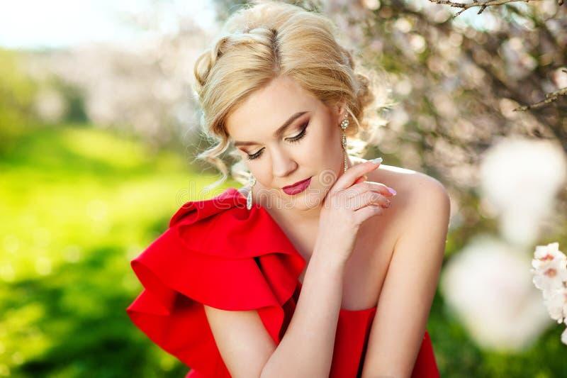 Mode, folk och begrepp för sommarferier - röd klänning för härlig kvinna som solbadar över grön blommande trädgårds- bakgrund royaltyfria bilder