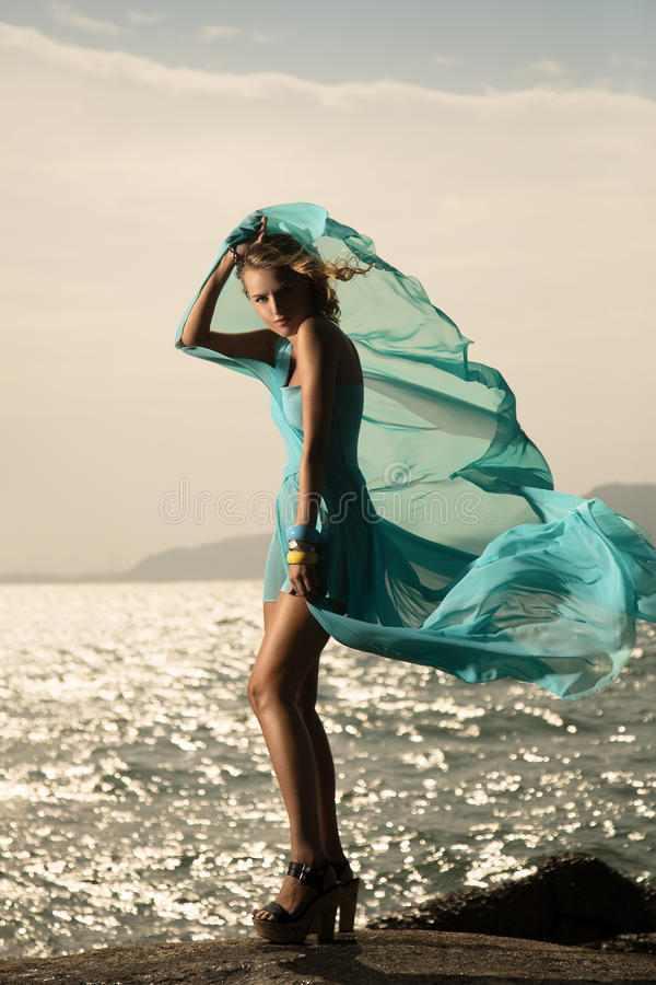 Mode-Frau in flatterndem blauem Kleid stockfotos