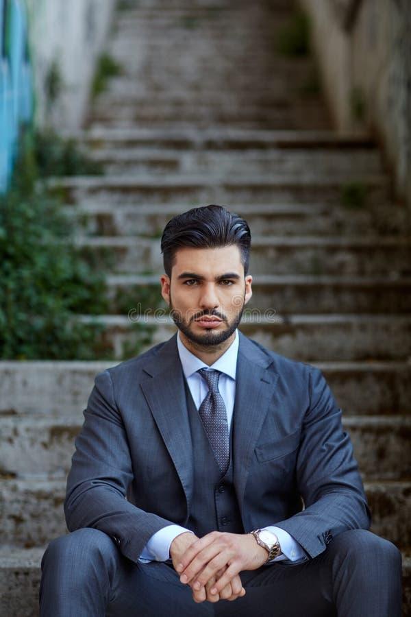 Mode-Geschäftsmann sitzt auf der alten Treppe lizenzfreie stockbilder