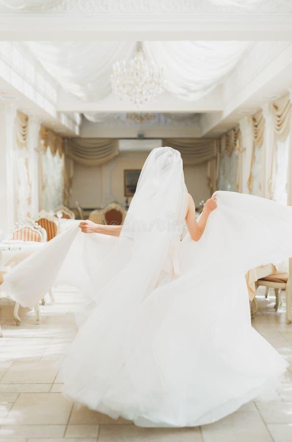 Mode-Hochzeitskleid der schönen Braut tragendes mit Federn mit Luxusfreudenmake-up und Frisur, Studio Innen stockfotos