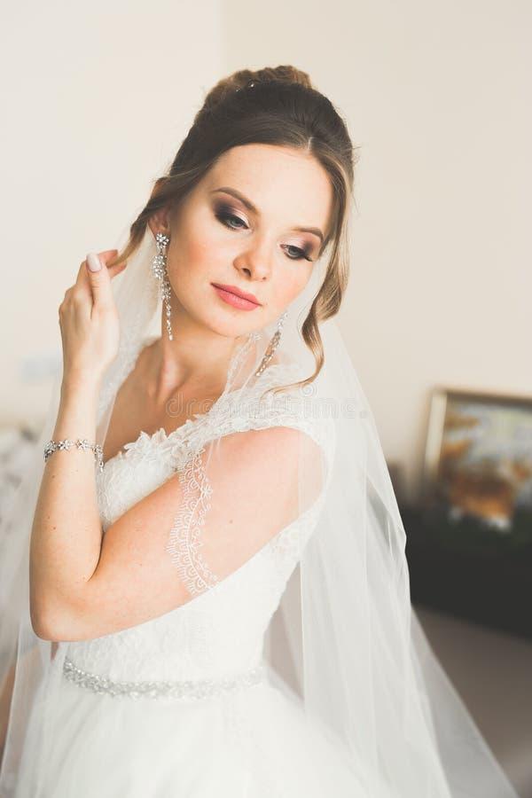 Mode-Hochzeitskleid der schönen Braut tragendes mit Federn mit Luxusfreudenmake-up und Frisur, Studio Innen stockbilder