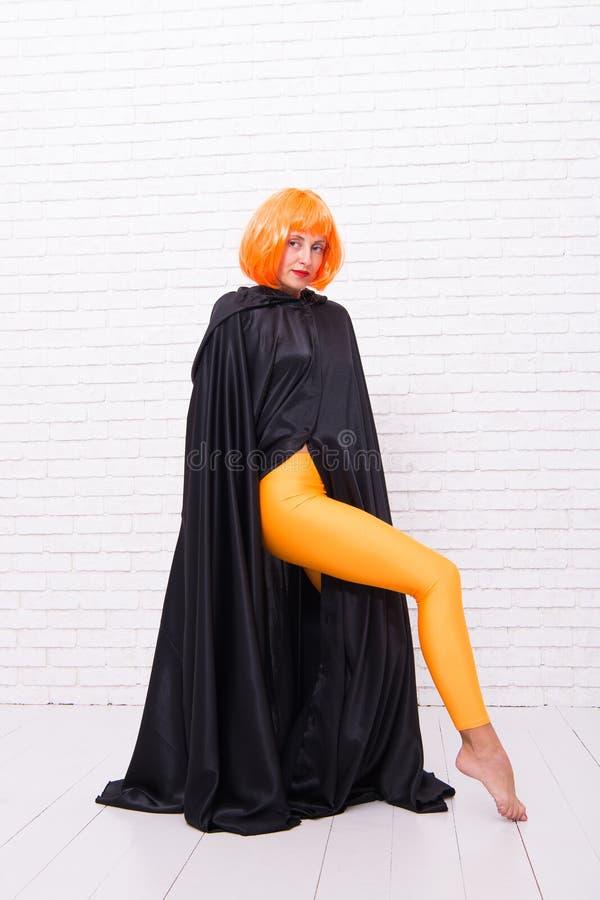 Mode ist ihr Leben Mode-Modell, das orange Perückenhaar und schwarze Robe auf weißem brickwall trägt Sexy M?dchen mit Mode stockfotos