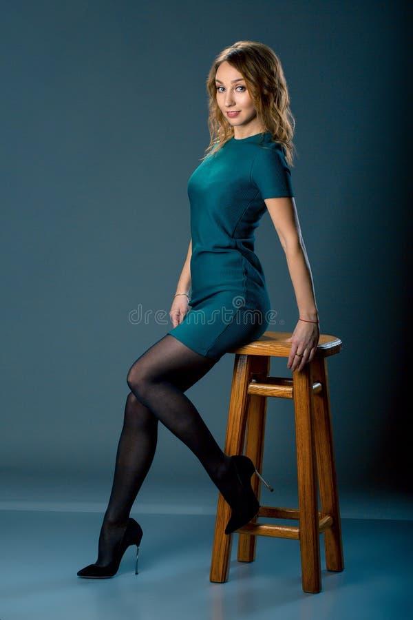 Mode klätt flickasammanträde på stol full längdstående Skönhetkvinna på mörk bakgrund arkivbild