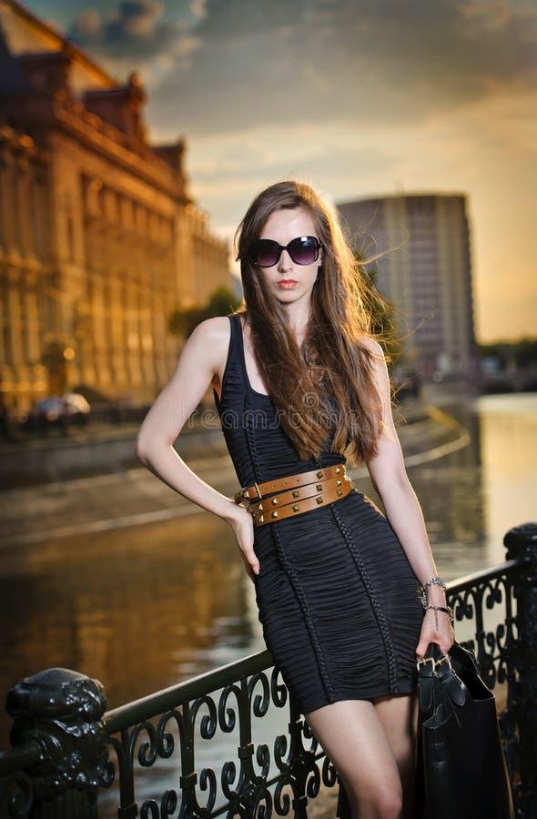 Mode-Modell auf der Straße mit Sonnenbrille und Kurzschlussschwarzes kleiden an stockbilder