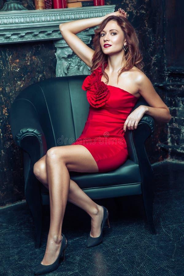 Mode-Modell, das im roten Kleid aufwirft lizenzfreie stockfotografie
