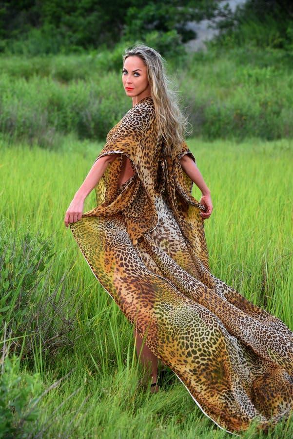 Mode-Modell, das an Rasenflächetragendem Tierdruck-Erholungsortkleid aufwirft lizenzfreie stockfotos