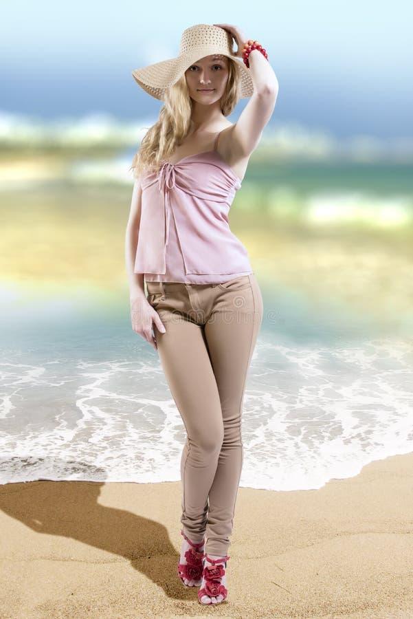 Mode-Modell, das stilvolle Sommerkleidung und -strohhut auf dem Strand trägt stockbilder