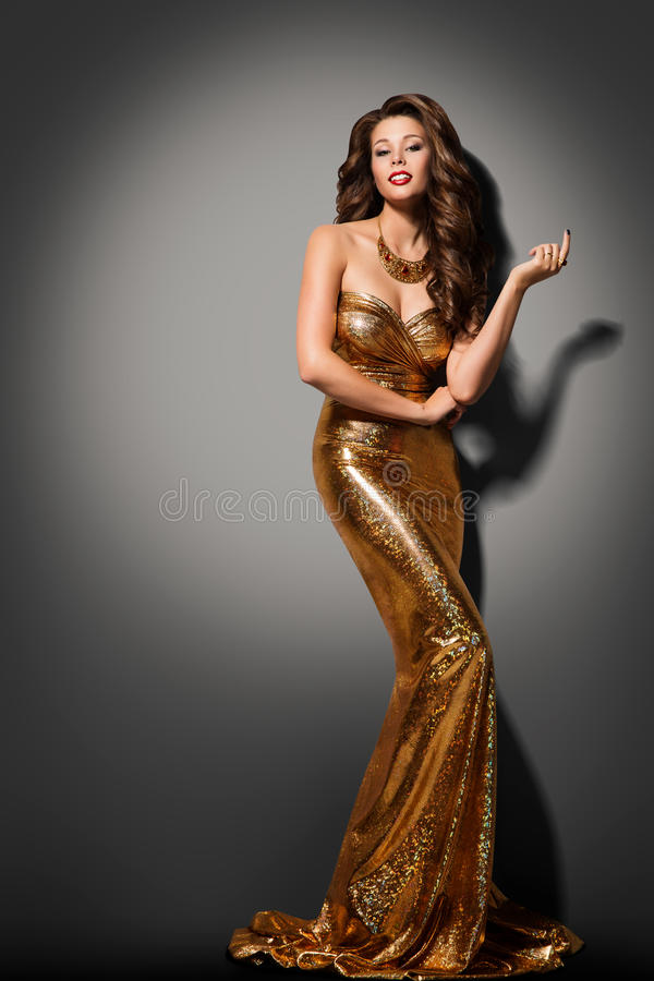 Mode-Modell-Girl Posing Glamour-Goldkleid, elegante Frauen-Kleid stockfotografie