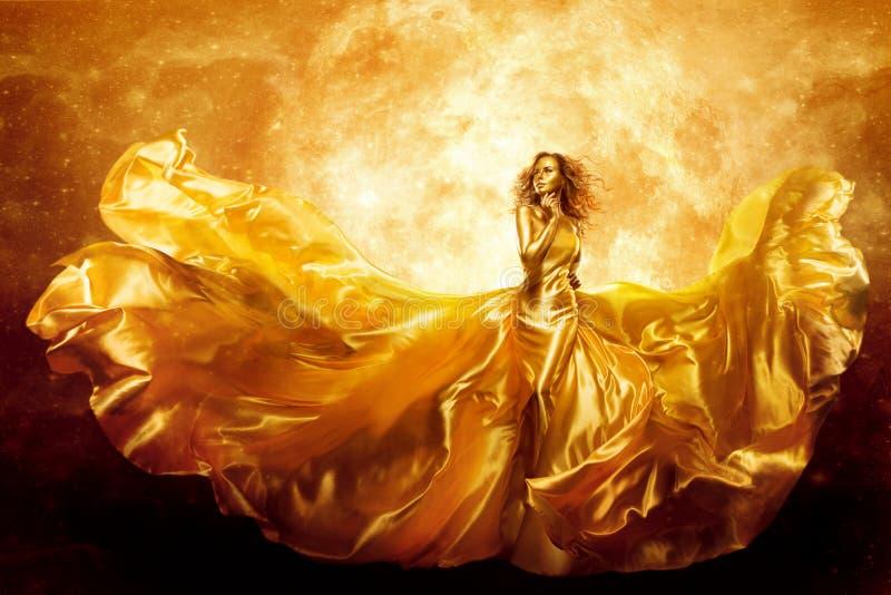 Mode-Modell Gold Color Skin, Fantasie-Frauen-Schönheit im künstlerischen wellenartig bewegenden Kleid, fliegendes Seiden-Kleid stockbild