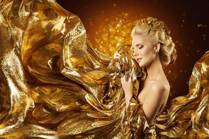 Mode-Modell Gold Fabric, Frauen-Gesicht und fliegender goldener Stoff stockfotos