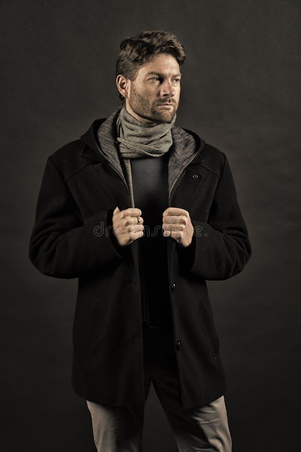 Mode-Modell-Haltung auf dunklem Hintergrund Zuf?lliger Mantel der Mannabnutzung mit Schal Herbst- oder Fallmodeausstattung Vertra lizenzfreie stockfotos