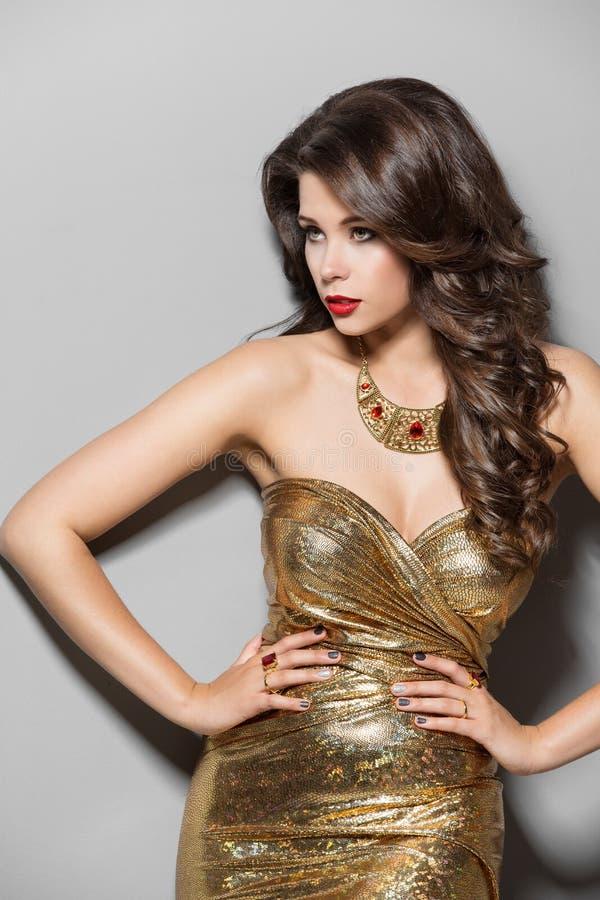Mode-Modell im Goldkleid, elegante Frauen-Schönheits-Porträt stockbild